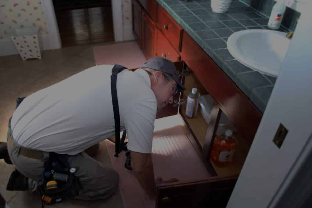 man looking under kitchen sink