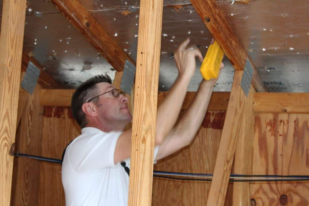 inspector looking under attic roof
