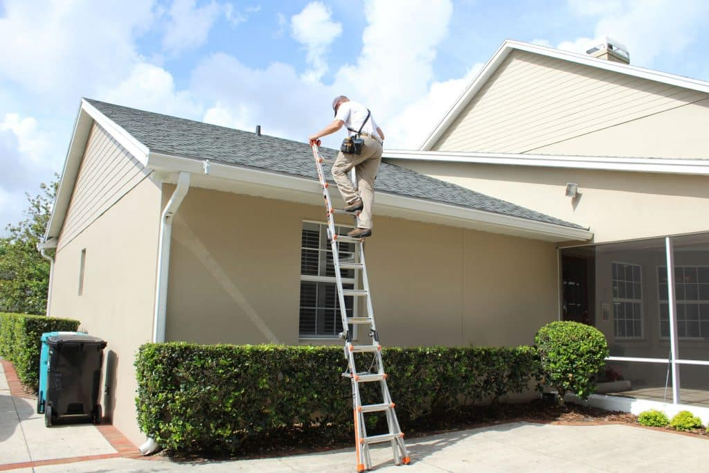 home inspector climbing ladder to roof