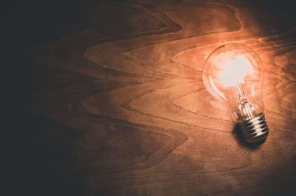 lit light bulb on wooden background