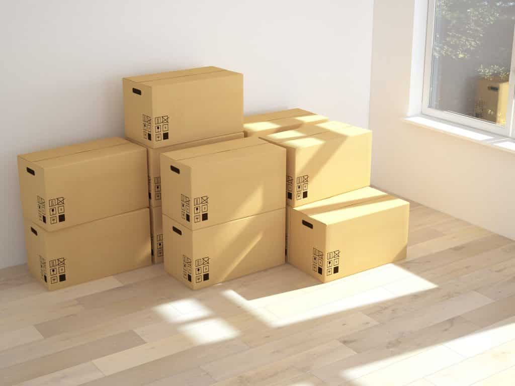 cardboard boxes stacked in corner of room