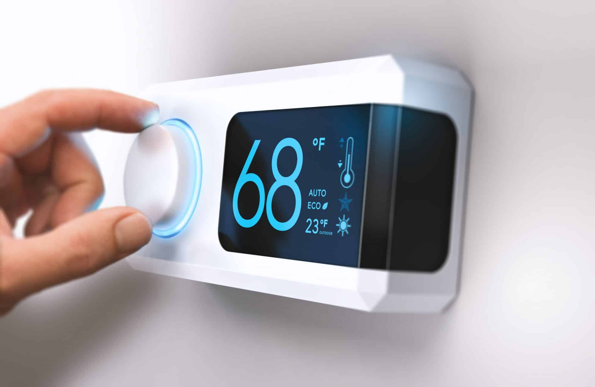 hand adjusting temperature on smart digital thermostat