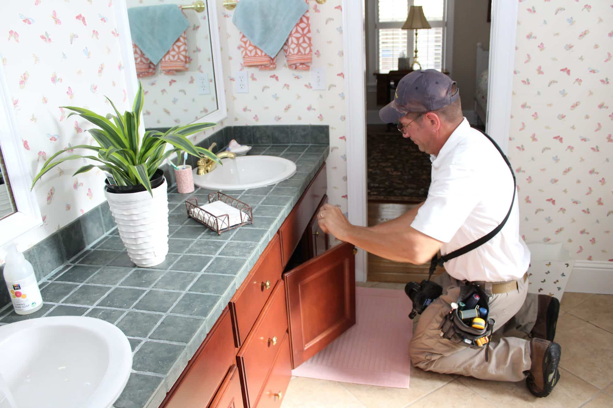 inspector looking under bathroom cabinets