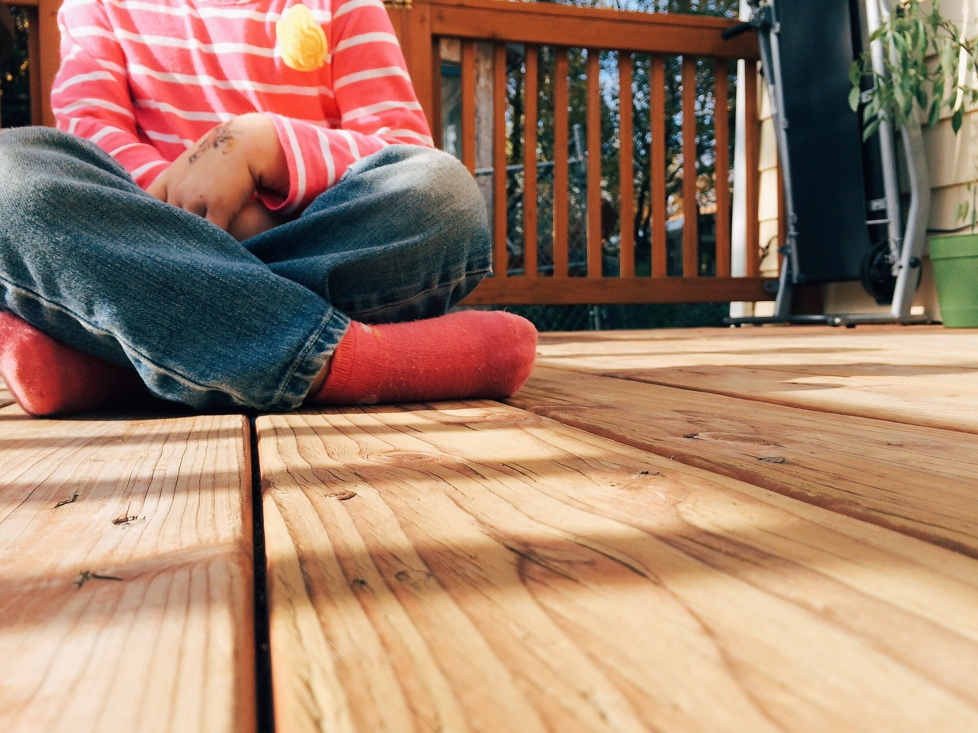 child sitting on outdoor deck