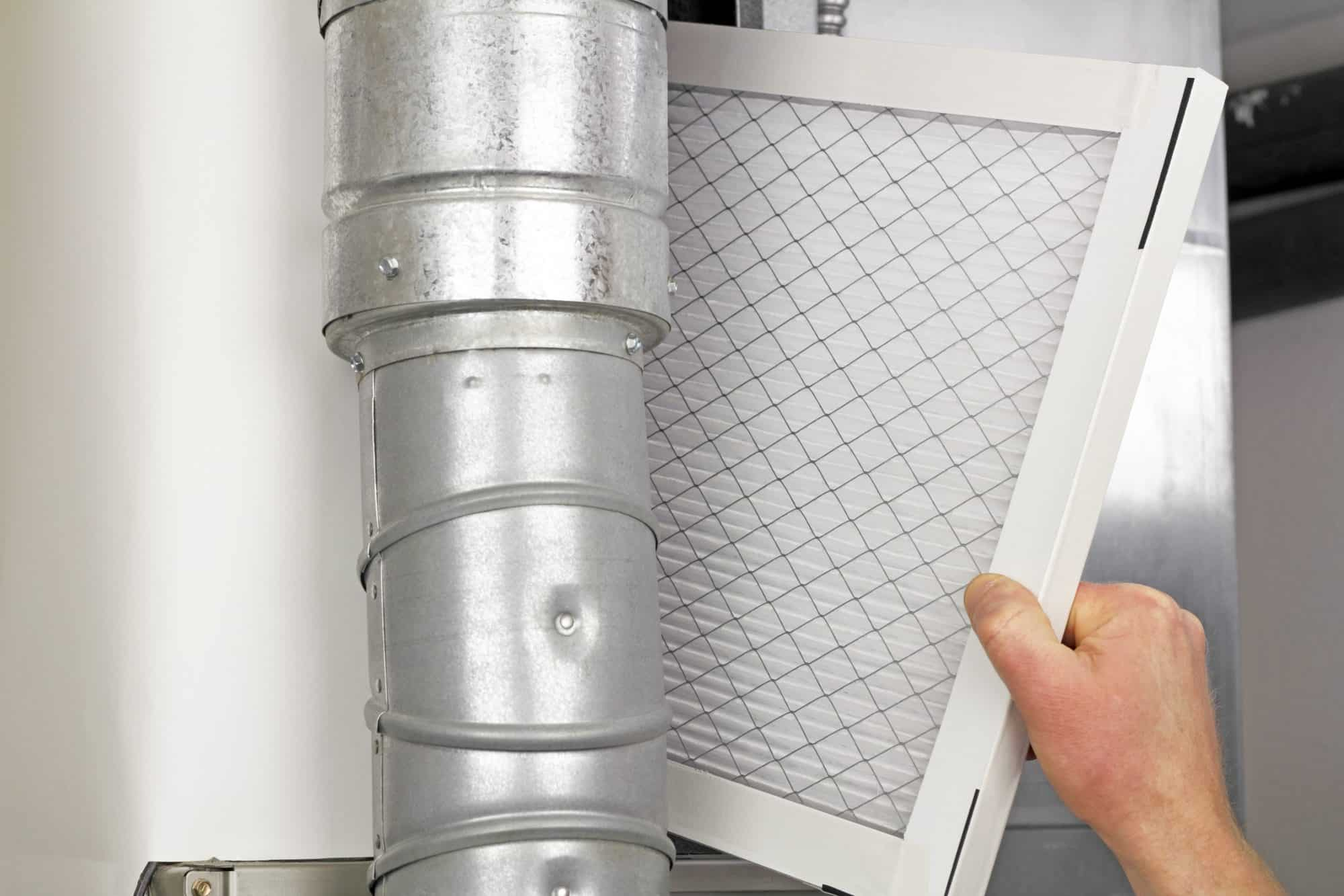 hand replacing home air filter for HVAC maintenance