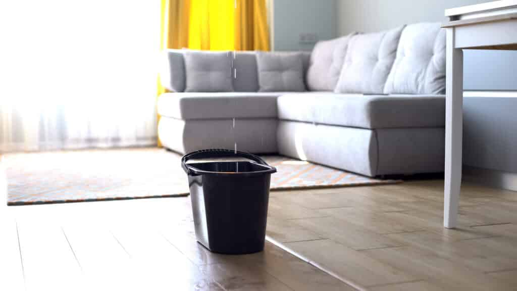 Bucket on floor catching water from leaky roof